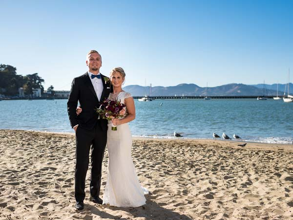 A bride and groom on the beach in San Francisco.